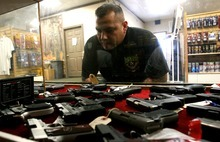Leah Hogsten  |  The Salt Lake Tribune Felipe Garcia looks for a Ruger .9mm in the pistol cases of Doug's Shoot 'N Sports Saturday in Taylorsville. Sales of guns at gun shops in Utah are closely regulated, but those selling firearms over the Internet through classifieds have few restrictions or regulations.