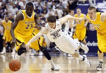 Trent Nelson  |  The Salt Lake Tribune Wyoming's Djibril Thiam knocks the ball loose from BYU's Jimmer Fredette as BYU hosts Wyoming, college basketball in Provo, Utah, Saturday, March 5, 2011. Wyoming's JayDee Luster at right.