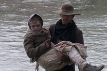 Levi Savage (Jasen Wade) carries a settler across the Platte River during a treacherous handcart journey to Utah in the drama