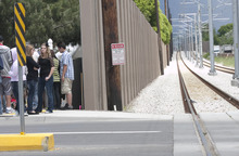 File photo  |  The Salt Lake Tribune Utah Transit Authority has decided to remove sections of sound wall that are obstructing pedestrian visibility at TRAX intersections on the the new Mid-Jordan line. This photo from last Thursday shows a group of friends gathered near a memorial placed at the site where Shariah Casper, 15, was struck and killed by a train the previous day.