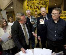 Al Hartmann  |  The Salt Lake Tribune   Merrill Cook, left, signs a petition to file at the Salt Lake County Clerk's office Tuesday to put measure on 2012 ballot for penalizing companies for hiring undocumented workers and getting rid of HB 116. Eli Cawley, right, of Utah Minuteman Project shows his Utah drivers license to crowd before signing the petition.