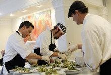 Sarah A. Miller  |  The Salt Lake Tribune Chef Adam Kreisel, center, and assistants Mark Benson, left, and Brian Coburn prepare salads for the By Invitation Only dinner held at the Maple Heights Condominium complex in Salt Lake City on May 28. By Invitation Only is an underground restaurant that takes place once a month in Salt Lake City and Park City. Kinnaird sets up a dinner at a different