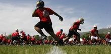 Trent Nelson  |  The Salt Lake Tribune High school football players run drills Thursday at the All-Poly Football Camp, held at Millcreek Junior High School.