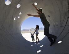 Al Hartmann  |  The Salt Lake Tribune Tara Thornely and Mathu Gaia explore the Sun Tunnels during Summer Solstice on Tuesday near Lucin with their son, Tama Gaia, 3.