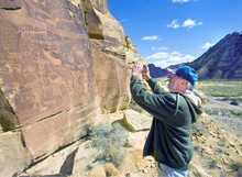 Al Hartmann  |  The Salt Lake Tribune Jochen Lahman, a tourist from Bergdorf, Germany, takes a picture of a rock art panel above the road in Nine Mile Canyon. He  started coming to the canyon to look at the rock art 25 years ago.
