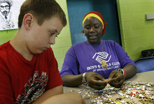 Scott Sommerdorf  |  The Salt Lake Tribune Hawa Abdi works with Michael Shaver, as they build a puzzle together at the Boys & Girls Club, Thursday, June 30, 2011. Abdi is one of 29 members of the Capitol West Boys & Girls Club who graduated from high school this year.