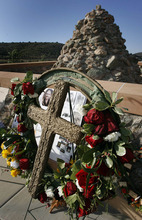 Tribune file photo Flowers and photos were placed at the Mountain Meadows Memorial site by descendants and loved ones of the victims of the massacre, during the Mountain Meadows Massacre Memorial near Enterprise. The site has been named a national landmark.