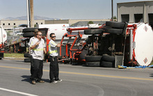 Scott Sommerdorf  |  The Salt Lake Tribune Workers talk about how best to right a tanker that collided with a train on Center Street in North Salt Lake, Monday, July 11, 2011. The impact tipped over the rear tanker of the truck, which was empty.