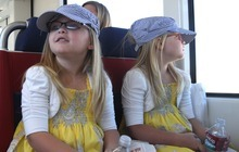 Rick Egan   |  The Salt Lake Tribune Twins, Emberly and Jocelynn Smith, 5, Magna, wear engineer caps as they ride the new Mid-Jordan TRAX line to Daybreak from Gardner Village on Friday. The test ride was offered to