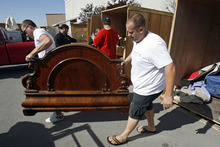 Francisco Kjolseth  |  The Salt Lake Tribune Chase Wiley, left, and friend Kameron Rollins, of Provo, do pretty well during a recent storage unit auction as they unload an ornate bed after landing a winning bid on two units at A-1 Pioneer Storage in North Salt Lake on July 2. The belongings of someone who has defaulted on their storage units could contain valuable items or things bound for the dump as people are only allowed to peek in and take a gamble on the value of what they can see.