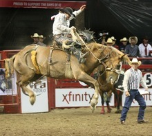 Paul Fraughton  |  The Salt Lake Tribune.Wade Sundell of Boxholm IA takes to the  air as he rides Sparrow Express  in the Saddle Bronc Riding competition on the opening night of the Days of 47 Rodeo at the Maverick Center on Monday  July 18, 2011