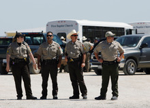 Officers stand at the entrance to the El Dorado Civic Center Friday, April 4, 2008, in El Dorado, Texas, after children were removed in the buses in the background from a nearby polygamist retreat.  Child welfare officials and state troopers removed a busload of children from the secretive West Texas religious retreat built by polygamist leader Warren Jeffs following a complaint to state authorities.  (AP Photo/Harry Cabluck)