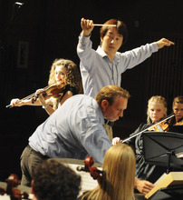 Guest violinist Jenny Oaks Baker (left), guest conductor David Cho and Lyceum Music Festival director Kayson Brown rehearse with the festival orchestra. Courtesy Photo