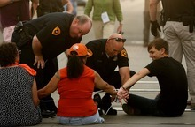 Leah Hogsten  |  The Salt Lake Tribune Protesters' plastic ties are cut apart so that police officers can walk each protester out of the intersection to be arrested. Police arrested 26 people during a demonstration that blocked traffic along Main Street on Tuesday in Salt Lake City.