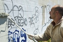 Chris Detrick | The Salt Lake Tribune  Using a paint roller, Jacob Shafizadeh removes graffiti from a wall in West Valley City Thursday July 21, 2011. His job is to remove graffiti from major roadways and public property.