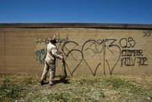 Chris Detrick | The Salt Lake Tribune  Jacob Shafizadeh paints over graffiti on a wall in West Valley City Thursday July 21, 2011. His job is to remove graffiti from major roadways and public property.