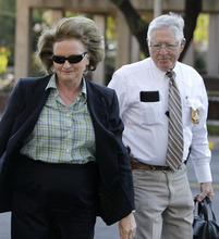 Tony Gutierrez  |  The Associated Press  District Judge Barbara Walther arrives at the Tom Green County Courthouse escorted by a law enforcement official Thursday in San Angelo, Texas. Walther is presiding over the trial of Polygamist sect leader Warren Jeffs, which began in earnest Thursday.