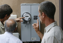 Scott Sommerdorf  |  The Salt Lake Tribune Olympus Cove resident Bob Frey, right, and others look at his meter box on Saturday as they discuss the benefits of his newly-installed solar system. Frey has installed a solar energy system on his home and held an open house. He projects that with rebates, tax incentives and the sale of excess power, he will make an 8 percent return on his investment. The Park City company DwellTek installed the system.