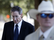 A law enforcement official stands by as Polygamist sect leader Warren Jeffs, left, arrives at the Tom Green County Courthouse, Thursday, July 28, 2011, in San Angelo, Texas. Jeffs' much-anticipated Texas trial begins in earnest Thursday, with prosecutors claiming he sexually assaulted girls he manipulated into