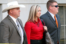 Rebecca Musser, a witness for the prosecution in the case against Warren Jeffs, leaves the Tom Green County Courthouse flanked by security Monday, Aug. 1, 2011 in San Angelo, Texas. Musser, who left the FLDS in 2002, was a wife of Rulon Jeffs, the former leader of the Fundamentalist Church of Jesus Christ of Latter Day Saints and father of Warren Jeffs. Musser testified on the importance of record-keeping in the sect. (AP Photo/San Angelo Standard-Times, Patrick Dove)