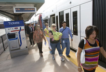 Al Hartmann  |  The Salt Lake Tribune Folks exit a new stepless TRAX train Tuesday onto the new West Valley Central Station platform after riding from the Daybreak Parkway Station in South Jordan as part of a two-part grand opening ceremony for both stations. The new lines open for commuters Sunday.