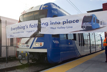 Al Hartmann  |  The Salt Lake Tribune A new stepless TRAX train breaks through a banner to open the Daybreak Parkway Station during a pre-kickoff ceremony Tuesday at Daybreak. The train contiued on to West Valley City to open the West Valley Central Station at 3650 South 2800 West.