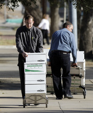 Members of the Fundamentalist Church of Jesus Christ of Latter-Day Saints arrive at Tom Green County Courthouse in San Angelo, Texas, rolling in boxes of materials for the defense in the sexual assault trial of polygamist leader Warren Jeffs on Thursday, Aug. 4, 2011. Jeffs, 55, is  accused of sexually assaulting two girls he took as brides during so-called