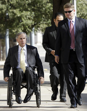 Texas Attorney General Greg Abbott,  left, arrives with members of his office at the Tom Green County Courthouse for proceedings in the sexual assault trial against polygamist religious leader Warren Jeffs Thursday Aug. 4, 2011, in San Angelo, Texas.   Jeffs, 55, is  accused of sexually assaulting two girls he took as brides during so-called