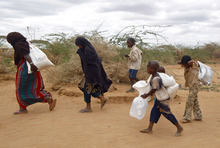 A newly arrived Somali family carry their supply of aid outside Dadaab, eastern Kenya, 100 kms (60 miles) from the Somali border, Friday Aug. 5, 2011. Somali government troops opened fire Friday in Mogadishu on hungry civilians, killing at least seven people, as both groups made a grab for food at a U.N. distribution site in the capital of this famine-stricken country, witnesses said. The drought and famine in the horn of Africa has  killed more than 29,000 children under the age of 5 in the last 90 days in southern Somalia alone, according to U.S. estimates. The U.N. says 640,000 Somali children are acutely malnourished, suggesting the death toll of small children will rise. (AP Photo/Jerome Delay)