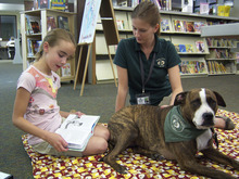 Natalie Dicou     Special to The Tribune Morningside Elementary School third-grader Sadie Bowen reads to Lucy, a therapy dog, at Holladay Library with Lucy's owner and trainer, Caitlin Thueson, of Therapy Dogs of Utah. Thueson brings the pit bull/boxer mix to the library every other Saturday so kids can practice their reading skills with a nonjudgmental listener.