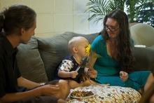 Chris Detrick     The Salt Lake Tribune Dave and Angelina Love watch as their son Moonee, 19 months, smells a sunflower in their apartment at the University of Utah Thursday August 18, 2011. Angelina Love calls for the expansion of breast-feeding laws in Utah and beyond.