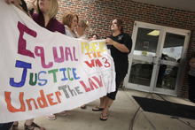 Women hold a sign at the Craighead County Court House in Jonesboro, Ark., Friday, Aug. 19, 2011, proclaiming innocence of three Arkansas men convicted in the 1993 deaths of three West Memphis, Ark., children. The three men convicted of the killings are at a hearing Friday that could end with their release from custody after nearly two decades in prison. (AP Photo/Danny Johnston)