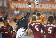 Houston Dynamo defender Bobby Boswell (32), right, heads the ball as Real Salt Lake goalkeeper Nick Rimando (18) defends against a corner kick by Dynamo midfielder Brad Davis (not pictured) during the first half of an Major League Soccer game at Robertson Stadium in Houston, Texas,  Saturday Aug. 20, 2011. (AP Photo/ Patric Schneider)