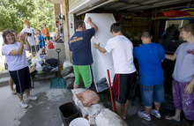 Tribune file photo by Al Hartmann Neighbors pitched in to move a refrigerator from the swamped garage of Murray residents Cheryl and Joel Leithead, who have filed a claim seeking compensation from a $165,000 fund set up by Salt Lake County.