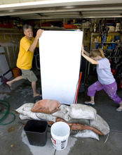 Al Hartmann  |  Tribune file photo Greg Sloan, left, helped neighbor Cheryl Leithead to move a refrigerator from her wet garage after a late July thunderstorm whose floodwaters resulted in Salt Lake County establishing a $165,000 fund to help residents pay for damages.