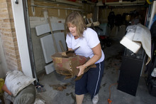 Al Hartmann  |  Tribune file photo Ruth Palmer moved a soaked box from her friend Cheryl Leithead's flooded garage after a July 26 cloudburst overwhelmed a broken storm drain. The Leitheads are among three dozen residents who have filed claims against the county, which has agreed to pay for roughly half of the damage.