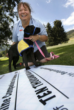 Scott Sommerdorf     The Salt Lake Tribune Wells Fargo awarded a $10k donation in honor of Barbara Kronenberg, of Riverton who volunteers for Canine Companions for Independence. She poses with Nyobi, a black Lab puppy in training to be an assistance dog, next to the ceremonial check for $10,000.