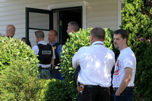 Josh Powell, foreground right, husband of missing Utah mother Susan Cox Powell, talks with one of approximately two dozen law enforcement office officers from the West Valley City Utah Police Department and Pierce County Sheriff's Department who are investigating leads in the two-year-old case, at the home of Josh's father, Steve Powell, in Puyallup, Wash., Thursday, Aug. 25, 2011. Two years after Susan Powell vanished, her case has spiraled into a salacious saga of finger-pointing and accusations of sex and lies between two sparring families. (AP Photo/The News Tribune, Dean J. Koepfler)