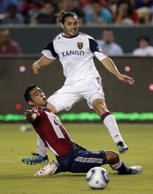 Real Salt Lake forward Fabian Espindola, top, watches his shot as he is defended by Chivas USA defender Michael Umana during the first half of an MLS soccer match at Home Depot Center in Carson, Calif., Saturday, Aug. 27, 2011. (AP Photo/Jae C. Hong)