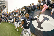Trent Nelson  |  The Salt Lake Tribune BYU defensive back Brian Logan (7) high-fives fans after the win, BYU vs. Wyoming, college football Saturday, October 23, 2010 at LaVell Edwards Stadium in Provo. BYU won 25-20.