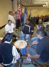 Al Hartmann  |  The Salt Lake Tribune Shoshone Nation Singers drum circle performs as a veteran from each of the Utah Indian tribes carry federal, state and tribal flags into the Native American Summit in Salt Lake City on Tuesday.