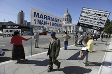A man walks past a group of people protesting against gay marriage outside a courtroom where the California Supreme Court was hearing arguments in San Francisco on Tuesday, Sept. 6, 2011. Although the legal challenge to California's same-sex marriage ban always has been assumed to be on track to reach the U.S. Supreme Court, the state's highest court is contemplating an issue that could halt the high-profile case in its tracks. (AP Photo/Eric Risberg)
