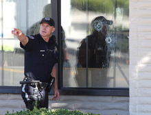 With bullet holes seen in a window, officers look for evidence at the scene of a shooting at an IHOP restaurant in Carson City, Nev., on Tuesday, Sept. 6, 2011. Three people were killed after a gunman opened fire at the restaurant, authorities said. (AP Photo/Cathleen Allison)