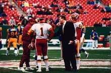 Trevor Matich (dark suit) on the field before a Redskins game. Courtesy Trevor Matich