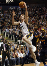 Photo by Chris Detrick | The Salt Lake Tribune  Utah Jazz small forward Gordon Hayward (20) shoots past Denver Nuggets center Nene (31) and Denver Nuggets point guard Ty Lawson (3) during the first half of the game at EnergySolutions Arena Thursday March 3, 2011.