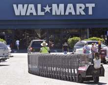 In this June 20, 2011 photo, a Wal-Mart worker pulls carts at a Wal-Mart store in Pittsburg, Calif. Wal-Mart Stores Inc. said Tuesday, Aug. 16, 2011, its second-quarter profit rose 5.7 percent, fueled by strong international sales and expense cutting. But the world's largest retailer still wasn't able to reverse a two-year U.S. sales slump. (AP Photo/Paul Sakuma)