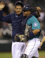 Seattle Mariners pitcher Felix Hernandez, left, greets Mariners catcher Miguel Olivo after the Mariners beat the Kansas City Royals 7-3 in a baseball game, Friday, Sept. 9, 2011 in Seattle. (AP Photo/Ted S. Warren)