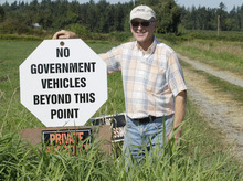 With the Canadian border less than a quarter-mile behind him, Larry DeHaan poses for a photo Wednesday, Sept. 7, 2011, on his dairy farm near Lynden, Wash. DeHaan has put up a sign asking government vehicles, such as those driven by the Border Patrol, to stay off of the portion of the road that is on his private property. The increased focus on border security since the Sept. 11, 2001 terrorist attacks has led to tensions between the government and local residents in the area. (AP Photo/Ted S. Warren)