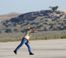 Al Hartmann  |  The Salt Lake Tribune Aircraft of the Manned-Unmanned System Integration Capability (MUSIC) was demonstrated at Dugway Proving Grounds on Thursday, Sept. 15.   Michael Reagan of AeraVironment launches a Raven, a small surveillance plane used in the demonstration.