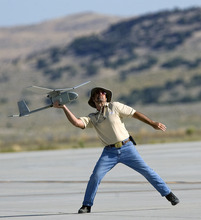 Al Hartmann  |  The Salt Lake Tribune Aircraft of the Manned-Unmanned System Integration Capability (MUSIC) was demonstrated at Dugway Proving Grounds on Thursday. Michael Reagan of AeraVironment launches by hand a Raven, a small surveillance plane used in the demonstration.